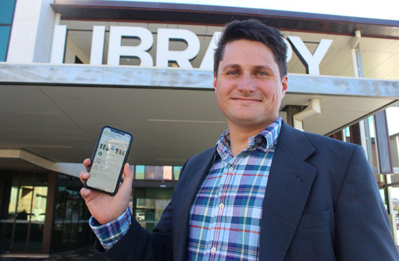 Cr Tim McMahon with new library APP on phone